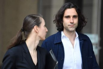 man with long black hair walking with woman holding clipboard|340x227