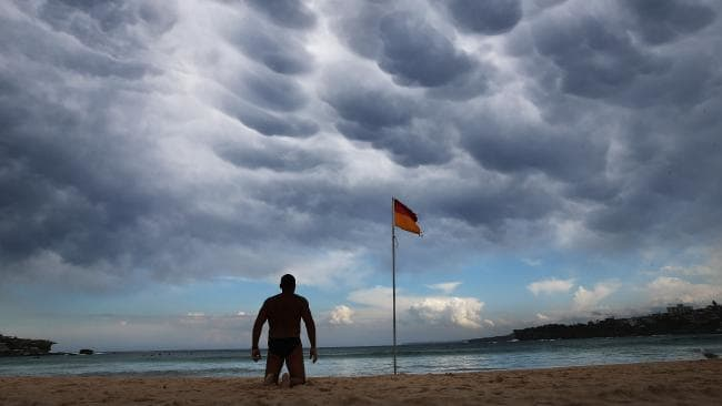 That's not actually Tony Abbott kneeling on a stormy beach, but feel free to pretend it is. Picture: Phil Hillyard