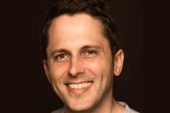 Headshot of Alex Turnbull, smiling, against a black background|340x227