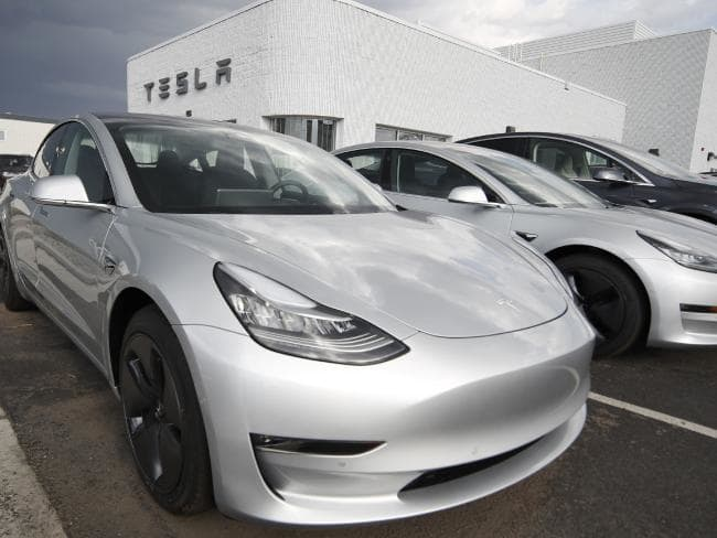 Tesla's Model 3 sedans sit on display outside a showroom. Tesla shares have dropped back to near the level they were trading at before CEO Elon Musk tweeted that he may take the company private. Picture: AP