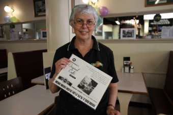 A cafe worker holds up an old-style menu. 340x227